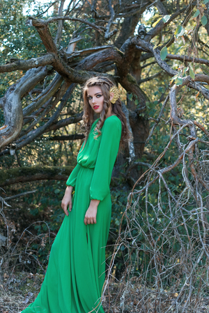 forest wood: beautiful sexy girl with long hair walking in the woods in a long green dress in the branches