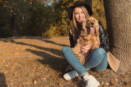 Beautiful cute happy girl in a black hat playing with her dog in a park in autumn another sunny day
