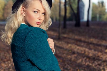 ropa de invierno: hermosa novia atractiva una niña feliz la rubia en una chaqueta y un sombrero camina en el parque de la ciudad en día soleado de otoño