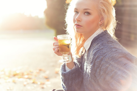 太陽の明るい光の晴れた秋の日に公園でお茶を飲んで暖かいセーターで金髪の美しい少女