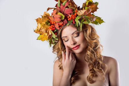 pelo rojo: manera del estilo de los retratos chica sexy hermosa con la caída de pelo rojo con una corona de hojas de color y maquillaje de moda de montaña de color ceniza brillante en tonos anaranjados