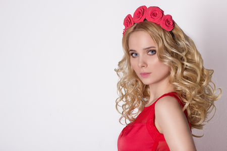 Fashionable portrait shot of a beautiful sexy girl in a cute blonde with curly hair wearing a wreath of flowers handmade in the evening image on a white background in studio