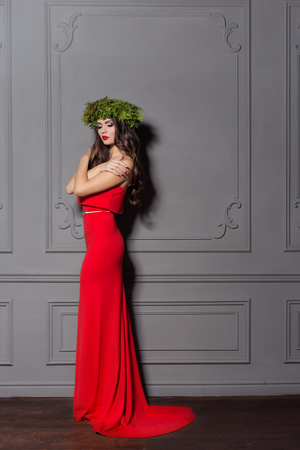 gorgeous woman: Christmas elegant fashion woman. Xmas New Year hairstyle and makeup. Gorgeous Vogue style Lady with Christmas decorations on her head, baubles, professional makeup, red lipstick long red evening dress
