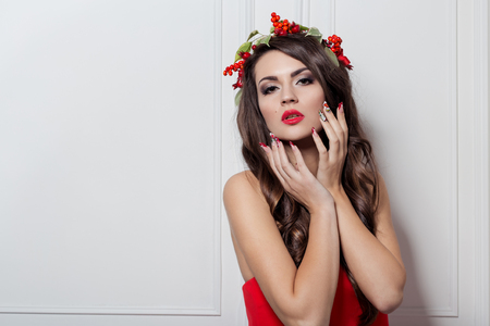 gorgeous: Christmas elegant fashion woman. Xmas New Year hairstyle and makeup. Gorgeous Vogue style Lady with Christmas decorations on her head, baubles, professional makeup, red lipstick long red evening dress