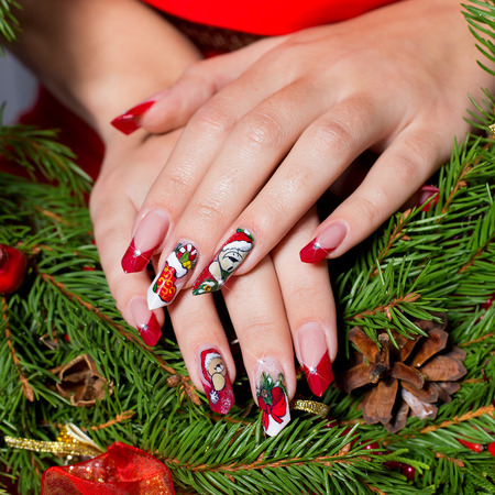 christmas manicure: beautiful well-groomed hands of a young girl with long fake acrylic nails with a festive Christmas pattern on the nails Stock Photo