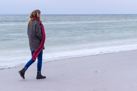 rubella: Lone sad beautiful girl walking along the shore of the frozen sea on a cold day, rubella, chicken with a red scarf on the neck