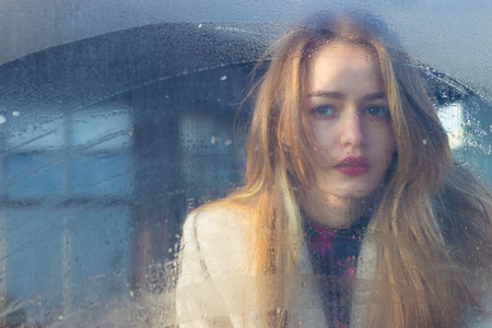 naked young woman: sad beautiful seksalnaya Pretty sad lonely girl behind wet glass with big sad eyes in a coat