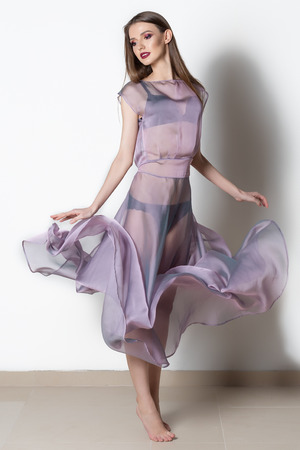 dress blowing in the wind: Fantastic fashion woman in a flowing transparent dress with bright makeup in studio