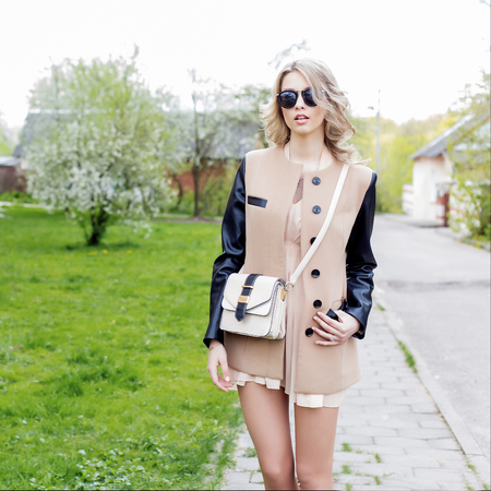 full lips: beautiful sexy girl with full lips walks in sunglasses in a coat with a handbag through the city streets