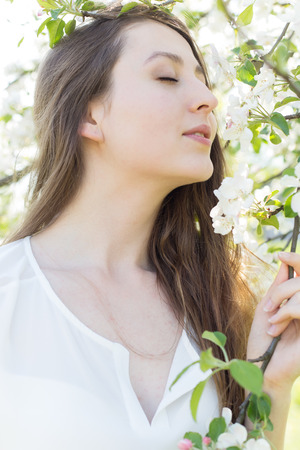 warm shirt: beautiful sweet girl in a white shirt with blooming apple trees in the garden walks bright warm summer day