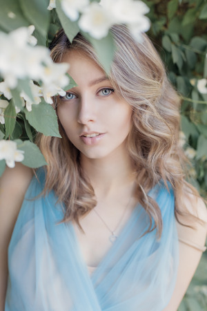 beautiful sweet tender girl with blue eyes in a blue dress with light hair stranded in jasmine flowers