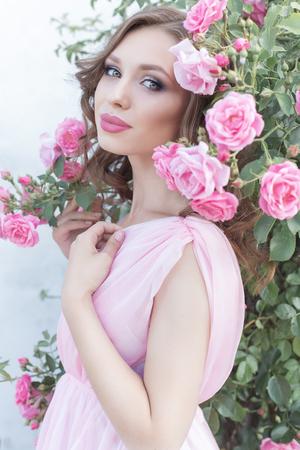 mujer con rosas: hermosa chica sexy en un vestido rosa de pie en las rosas de jardín en un día de verano soleado brillante con un suave maquillaje y brillantes grandes labios hinchados