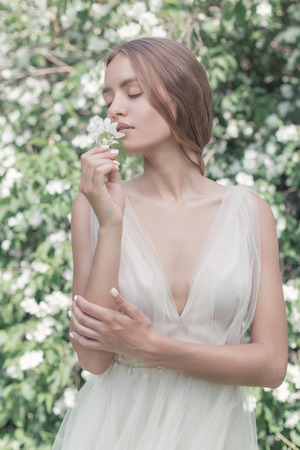 beautiful sexy girl bride in a light dress with delicate make-up and hair in the flower garden jasmine. Styled photo fane art