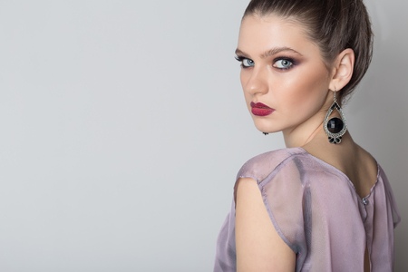 fashion portrait of a young beautiful girl in a light transparent dress with a bright evening make-up and hairstyle