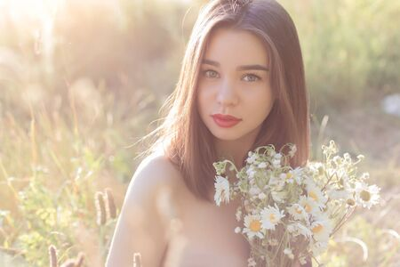 full lips: beautiful sweet girl with full lips sitting in a field with a bouquet of daisies with obnozhennymi shoulders at sunset in the sunlight Stock Photo