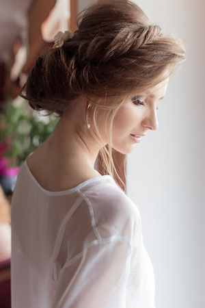 morning beautiful happy young girl of the bride near a window in a white dress with a beautiful boudoir evening festive hairdo with ornaments in their hair and soft makeup