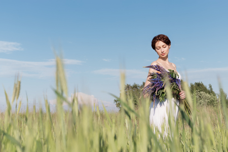 beautiful sweet girl with a plait hair in a white summer sundress walking in a field with a bouquet of purple lupine flowers