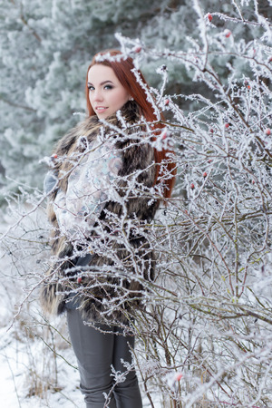 fur trees: beautiful gentle girl with red hair in a fur vest standing in a snowy forest with iniem on the branches of trees