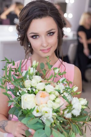 beautiful sweet girl bridesmaid preparing for the wedding of a friend in the pink evening dress with evening hairstyle and bright make-up with a bouquet of brides hands Stock Photo