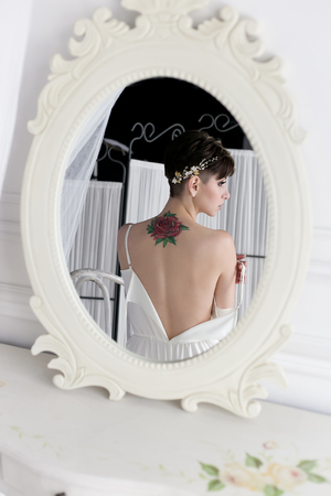 peignoir: Beautiful tender sexual girl bride with a short haircut gentle wreath on her head with a tattoo on her back in the linen near the mirror