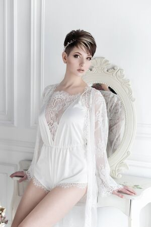 Beautiful tender sexual girl bride with a short haircut gentle wreath on her head with a tattoo on her back in the linen near the mirror