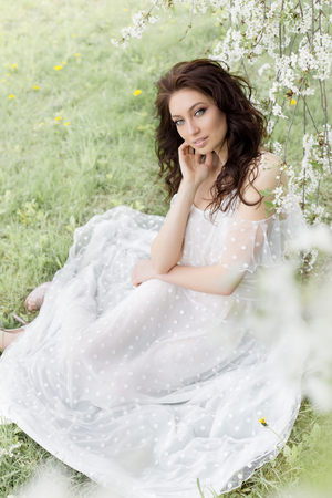 Beautiful sexy girl with a gentle make-up in a long light dress among the flowering trees walks in the spring garden on a warm sunny day Stock Photo
