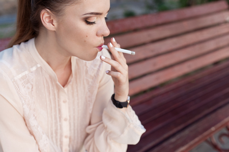 Beautiful young sad lonely girl sitting with a cigarette in hands on bench in park and smokes