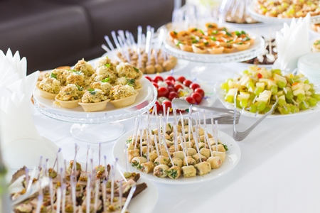 A small table with a delicious buffet of canapes, caviar, sandwiches Stock Photo