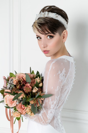 Beautiful tender sexy bride girl with short haircut with crown on head with bouquet of flowers and elegant wedding dress
