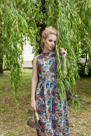 stands: Beautiful sweet tender girl blonde with blue eyes stands near a tree with long branches with a sprig of flowers in her hands