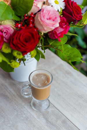 cup of hot coffee with milk stands near the window and a bright colored bouquet of flowers Stock Photo