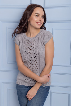beautiful cute girl with a smile demonstrates knitted clothes
