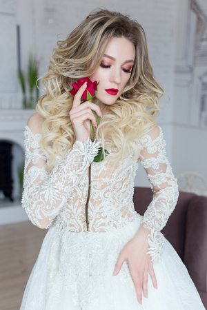 beautiful gentle bride in a chic wedding dress with flowers in her hands is photographed in a bright apartment Stock Photo