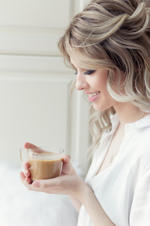 beautiful cute girl near the window in the morning in a white shirt with a cup of coffee Stock Photo