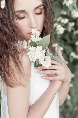beautiful cute tender girl with dark hair in a white summer dress with a jasmine flower in hands