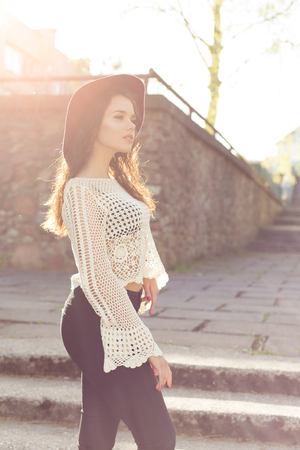 beautiful cute girl with curly hair in a hat walking at sunset around the city
