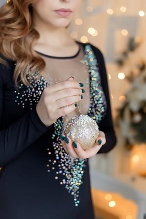 beautiful sweet girl in evening dress near Christmas tree unpacks presents Banco de Imagens