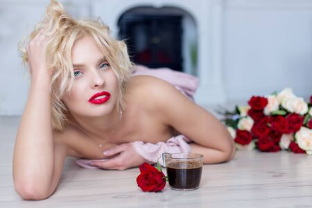 beautiful blond girl lies on the floor with a cup of hot morning coffee and a bouquet of roses