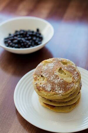 pancakes with berries and powdered sugar in a white plate are on the table