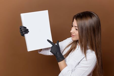 girl medical worker in black gloves in a white suit with a magazine in her hands