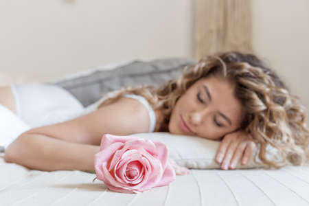 beautiful girl with curly hair in a white bodysuit with a rose lies on the bed