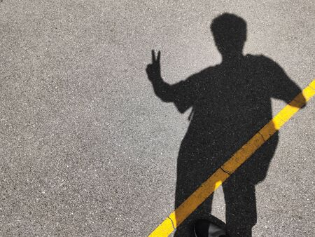 A man and peace finger sign shadow Foto de archivo - 134877142