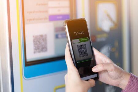 Une fille scanne le code QR pour acheter le billet de train Banque d'images