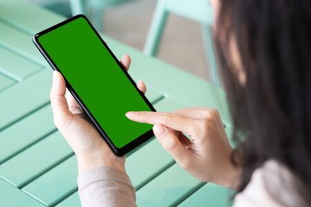 A woman and green screen on black smartphone