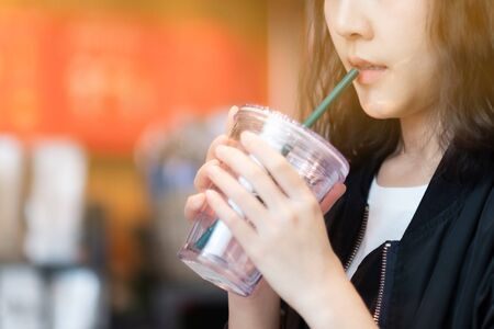 A woman drinking coffee by reuse coffee glass in coffee cafe  Stock Photo