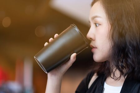 A woman drinking coffee by reuse black coffee bottle in coffee cafe Stock Photo