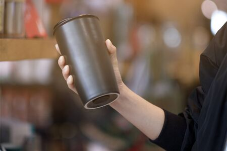A woman holding reuse black coffee bottle in coffee cafe Stock Photo