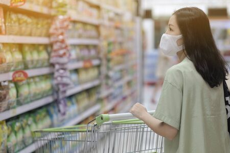 Asian women and surgical mask shopping some food in supermarket, covid-19 crisis