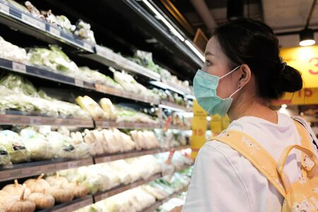 Asian girl in with t-shirt with yellow bag wear surgical mask to protect the Covid-19 in supermarket, New normal lifestyle Foto de archivo