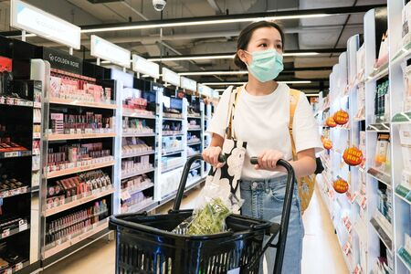 Asian girl in with t-shirt with yellow bag wear surgical mask to protect the Covid-19 in supermarket, New normal lifestyle